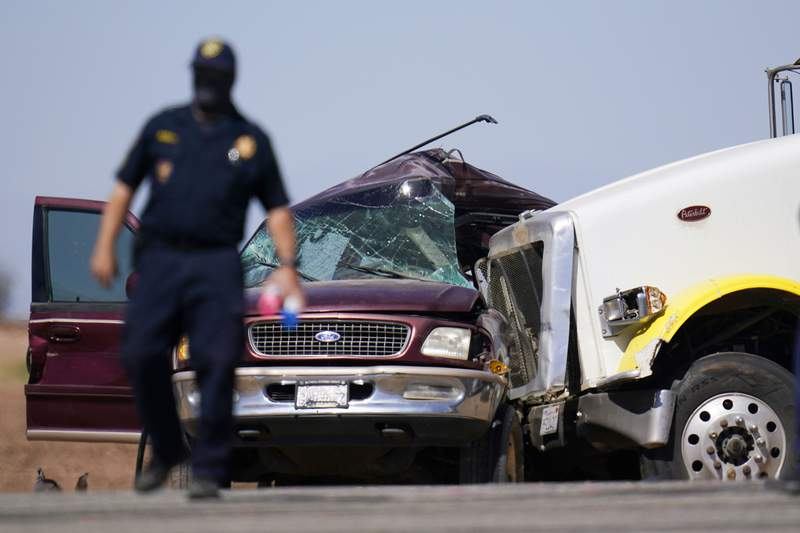 Law enforcement officers work at the scene of a deadly crash in Holtville, Calif., on Tuesday, March 2, 2021. Authorities say a semi-truck crashed into an SUV carrying multiple people on a Southern California highway, killing at least 13 people and injuring others. (AP Photo/Gregory Bull)