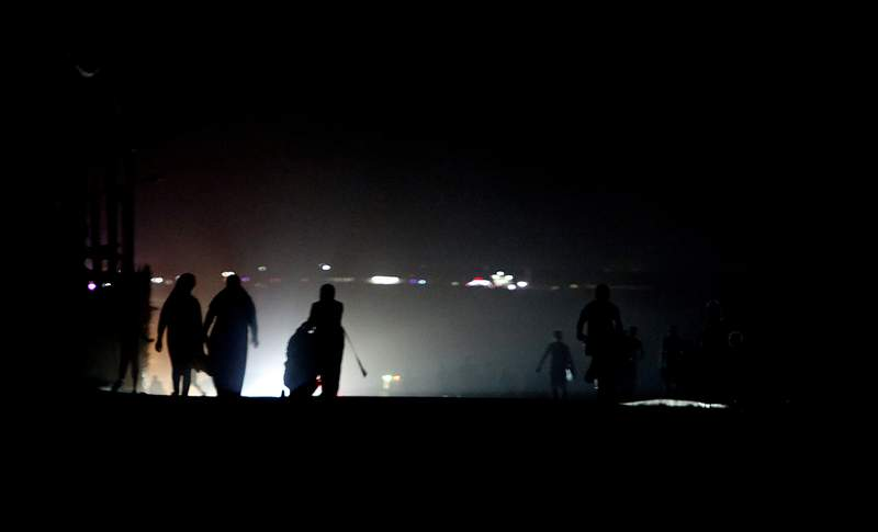 Palestinian residents walk in the Shati refugee camp in west Gaza City as the coastal enclave gets maximum four hours of electricity a day, Wednesday, Aug. 19, 2020. (AP Photo/Hatem Moussa)