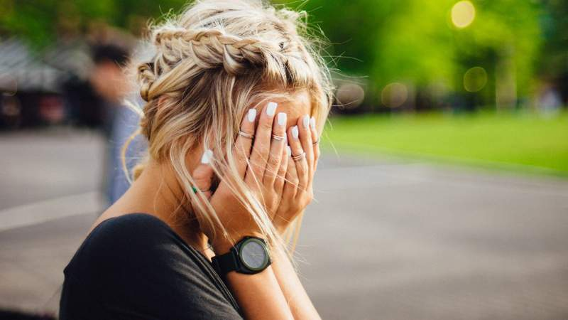 A woman holds her head in her hands.