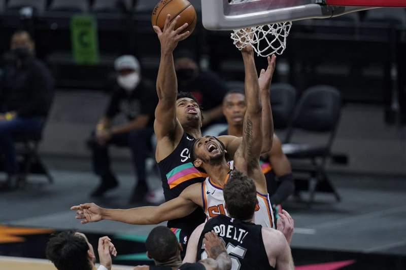 San Antonio Spurs forward Keldon Johnson, rear, reaches over Phoenix Suns guard Cameron Payne, center, for a rebound during the first half of an NBA basketball game in San Antonio, Sunday, May 16, 2021.
