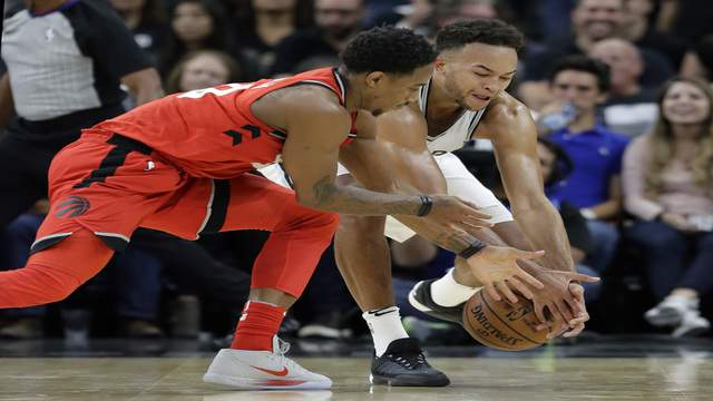 Toronto Raptors guard DeMar DeRozan, left, and San Antonio Spurs guard Kyle Anderson, right, scramble for a loose ball during the second half of an NBA basketball game, Monday, Oct. 23, 2017, in San Antonio. San Antonio won 101-97. (AP Photo/Eric Gay)