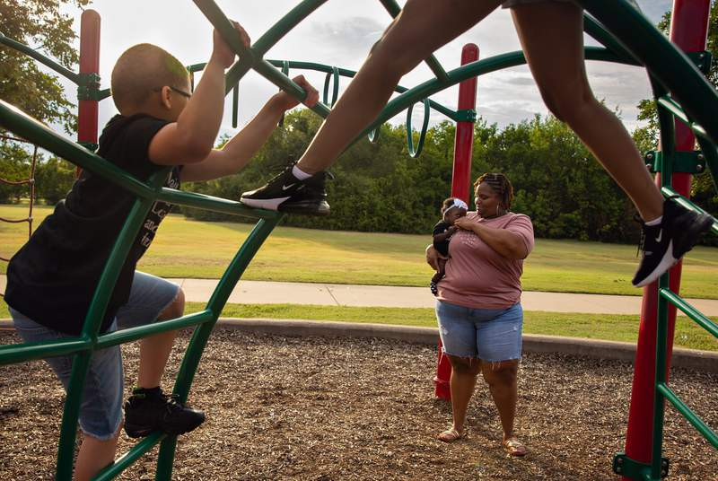 Tambra Morrison holds her 7-month-old daughter Kalani as they watch her other two children, Kayden and Kynnedi, climb the jungle gym at Red Bird Park in Duncanville on Aug. 14, 2021.
