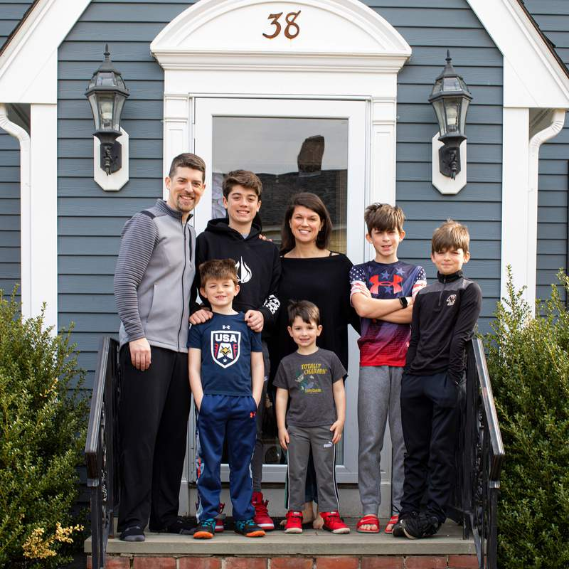 A family with five boys poses in front of their home as a part of The Front Steps Project.