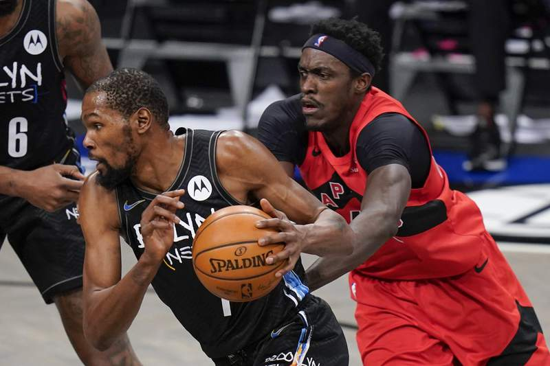 Brooklyn Nets' Kevin Durant, left, drives past Toronto Raptors' Pascal Siakam during the first half of an NBA basketball game Friday, Feb. 5, 2021, in New York. (AP Photo/Frank Franklin II)