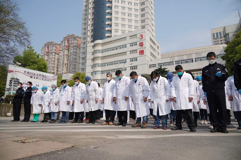 """In this photo released by China's Xinhua News Agency, medical workers bow their heads during a national moment of mourning for victims of coronavirus in Wuhan in central China's Hubei Province, Saturday, April 4, 2020. With air raid sirens wailing and flags at half-staff, China on Saturday held a three-minute nationwide moment of reflection to honor those who have died in the coronavirus outbreak, especially """"martyrs"""" who fell while fighting what has become a global pandemic. (Cai Yang/Xinhua via AP)"""