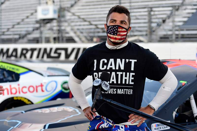 """MARTINSVILLE, VIRGINIA - JUNE 10: Bubba Wallace, driver of the #43 Richard Petty Motorsports Chevrolet, wears a """"I Can't Breathee - Black Lives Matter"""" t-shirt under his fire suit in solidarity with protesters around the world taking to the streets after the death of George Floyd on May 25, speaks to the media prior to the NASCAR Cup Series Blue-Emu Maximum Pain Relief 500 at Martinsville Speedway on June 10, 2020 in Martinsville, Virginia. (Photo by Jared C. Tilton/Getty Images)"""