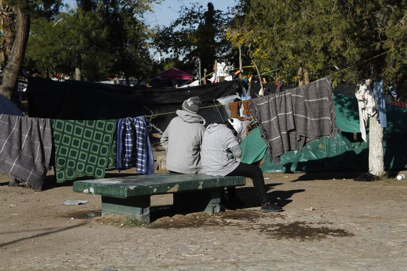 FILE - In this Dec. 3, 2019, file photo, Luis, left, a migrant fleeing gang violence in Michoacan, sits with his 13-year-old son on a bench in a public park facing a tent camp for refugees in Juarez, Mexico. Luis' family has lived in the camp for two months while they wait to apply for asylum in the U.S., at a border crossing about a quarter of a mile away. The Supreme Court on Wednesday, March 11, 2020, said it would allow the Trump administration to continue enforcing a policy that makes asylum-seekers wait in Mexico for U.S. court hearings, despite lower court rulings that the policy probably is illegal. (AP Photo/Cedar Attanasio, File)
