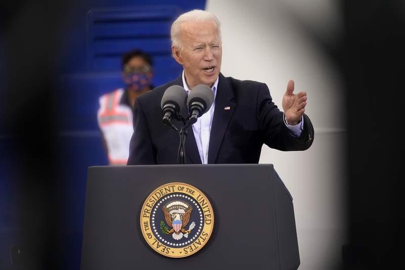 In this image taken through scaffolding, President Joe Biden speaks at a FEMA COVID-19 mass vaccination site at NRG Stadium, Friday, Feb. 26, 2021, in Houston. (AP Photo/Patrick Semansky)
