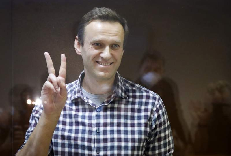 FILE - In this Saturday, Feb. 20, 2021 file photo, Russian opposition leader Alexei Navalny gestures as he stands in a cage in the Babuskinsky District Court in Moscow, Russia. Navalny marked the anniversary of a poisoning attack against him on Friday, Aug. 20 by urging global leaders to step up fight against corruption and target tycoons close to Russian President Vladimir Putin. (AP Photo/Alexander Zemlianichenko, file)