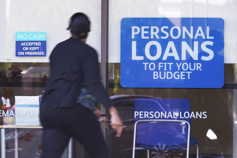 A woman walks past a personal finance loan office Thursday, Oct. 1, 2020, in Franklin, Tenn.  U.S. consumers cut back on their borrowing in August, with credit card use dropping for a sixth straight month, reflecting caution in the midst of the pandemic-triggered recession. The Federal Reserve said Wednesday, Oct. 7,  that total borrowing fell by $7.2 billion after a gain of $14.7 billion in July. (AP Photo/Mark Humphrey)