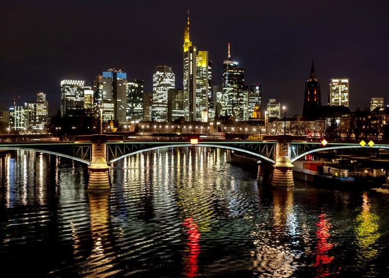 The lights of a bridge are reflected in the river Main in Frankfurt, Germany, Thursday, Jan. 21, 2021. In background are the buildings of the banking district. (AP Photo/Michael Probst)
