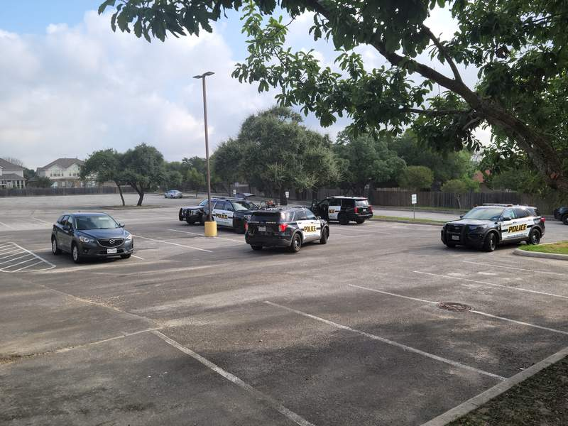 Police gather in a parking lot on DeZavala Road after capturing three teen robbery suspects.