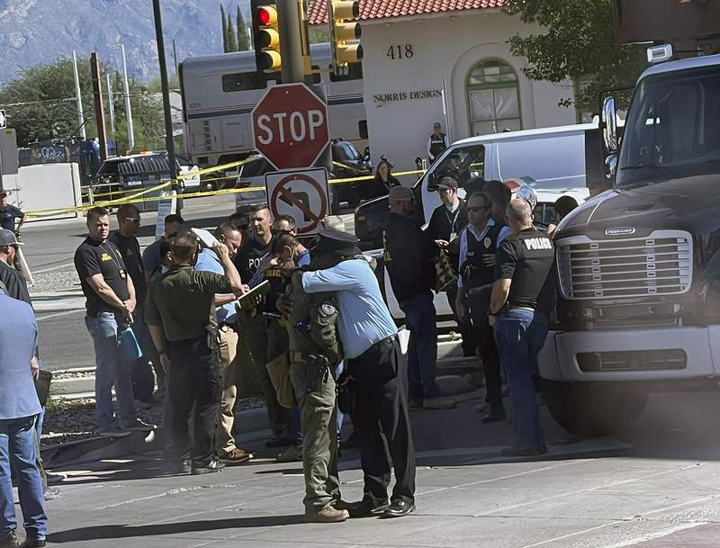 This photo provided by Evan Courtney shows two officers embracing near the scene of a shooting aboard an Amtrak train in Tucson, Ariz., Monday, Oct. 4, 2021. One person is in custody after someone opened fire Monday aboard an Amtrak train in Tucson, Arizona, police said. The shooting happened just after 8 a.m. on a train parked at the station in the city's downtown. Authorities say the scene has been secured and no threat remains. (Evan Courtney via AP)