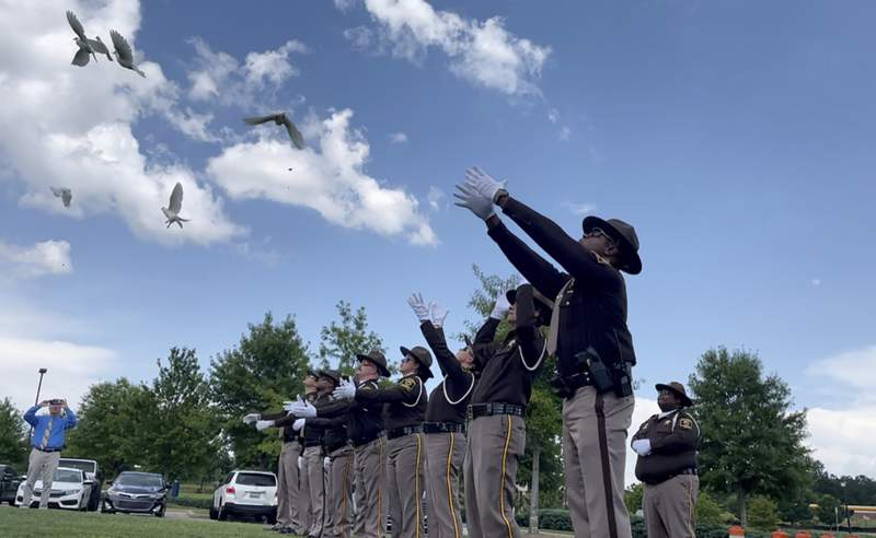 FILE - Sheriff's deputies release white doves for the young victims of a fatal car crash outside a church where the public memorial service was held Thursday, July 15, 2021, in Auburn, Ala. A crash that killed 10 people  including nine children  on a rain-slicked Alabama interstate happened after a tractor-trailer truck slammed into vehicles that had slowed down because of minor crashes, according to a preliminary report released Tuesday, Aug. 3, 2021. (AP Photo/Kim Chandler)