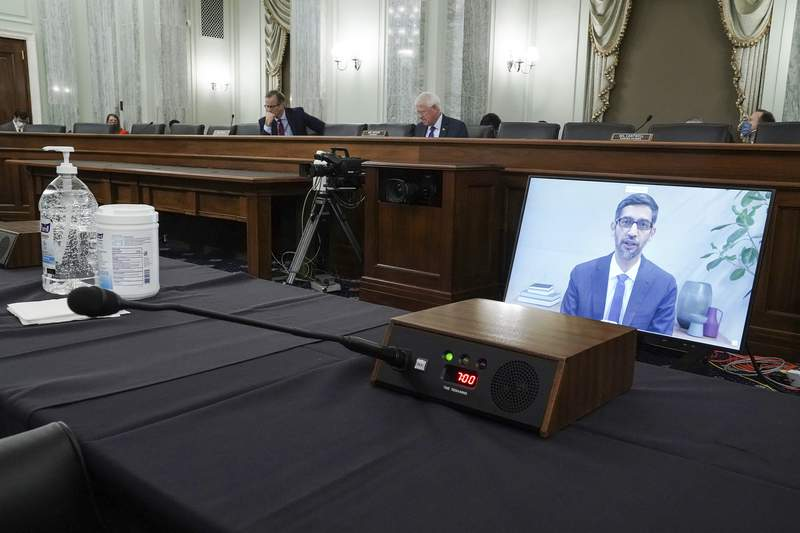 FILE - In this Oct. 28, 2020 file photo, Google's CEO Sundar Pichais appears on a screen as he speaks remotely during a hearing before the Senate Commerce Committee on Capitol Hill  in Washington.  Groundbreaking legislation is advancing in Congress, Friday, June 25,  that would curb the market power of tech giants Facebook, Google, Amazon and Apple. The bill could force them to untie their dominant platforms from their other lines of business.    (Greg Nash/Pool via AP, File)