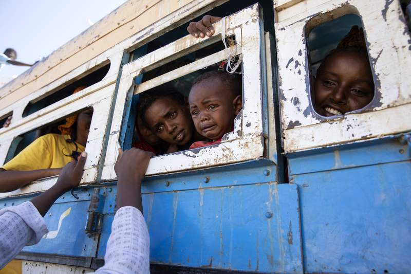"""FILE - In this Tuesday, Dec. 1, 2020 file photo, refugees who fled the conflict in Ethiopia's Tigray region ride a bus going to the Village 8 temporary shelter, near the Sudan-Ethiopia border, in Hamdayet, eastern Sudan. Life for civilians in Ethiopia's embattled Tigray region has become """"extremely alarming"""" as hunger grows and fighting remains an obstacle to reaching millions of people with aid, the United Nations said in a new report released late Thursday, Feb. 4, 2021. (AP Photo/Nariman El-Mofty, File)"""