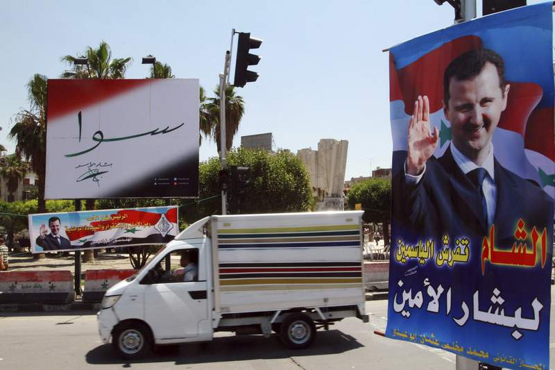 """FILE - In this May 12, 2014 file photo, campaign posters for the upcoming presidential election adorn a street in Damascus, Syria. On Monday April 26, 2021, the Paris-based Syrian Network for Human Rights called on the international community to reject presidential elections in the war-torn country scheduled for May, describing them as a sham because they will take place under President Bashar Assad, who is implicated in war crimes. Arabic on the poster, right, reads, """"Damascus spreads flowers for the loyal Bashar."""" The banner reads, """"Together with Bashar Assad."""" (AP Photo, File)"""