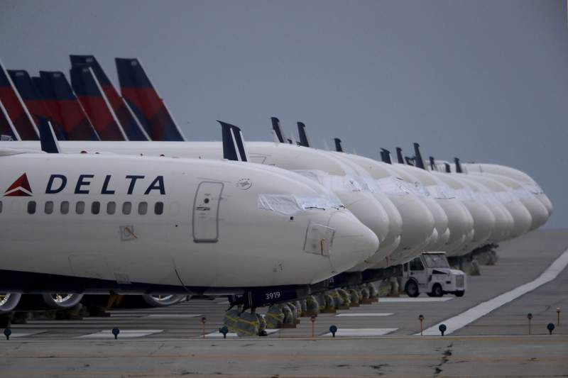 FILE - In this May 14, 2020 file photo, several dozen mothballed Delta Air Lines jets are parked on a closed runway at Kansas City International Airport in Kansas City, Mo.   Delta Air Lines says it lost $1.2 billion in the first quarter, but the airline thinks it can by profitable by late summer unless there's a resurgence of COVID-19. Delta reported the results on Thursday, April 15, 2021.  (AP Photo/Charlie Riedel, File)