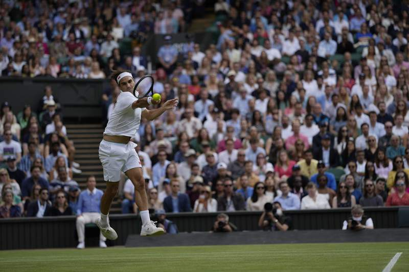 Switzerland's Roger Federer plays a return during the men's singles third round match against Britain's Cameron Norrie on day six of the Wimbledon Tennis Championships in London, Saturday July 3, 2021. (AP Photo/Alastair Grant)