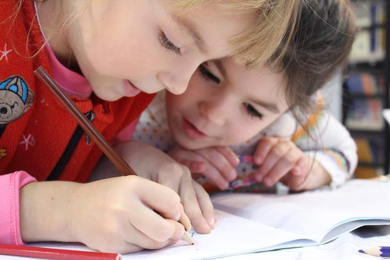 Two young girls write in a notebook.