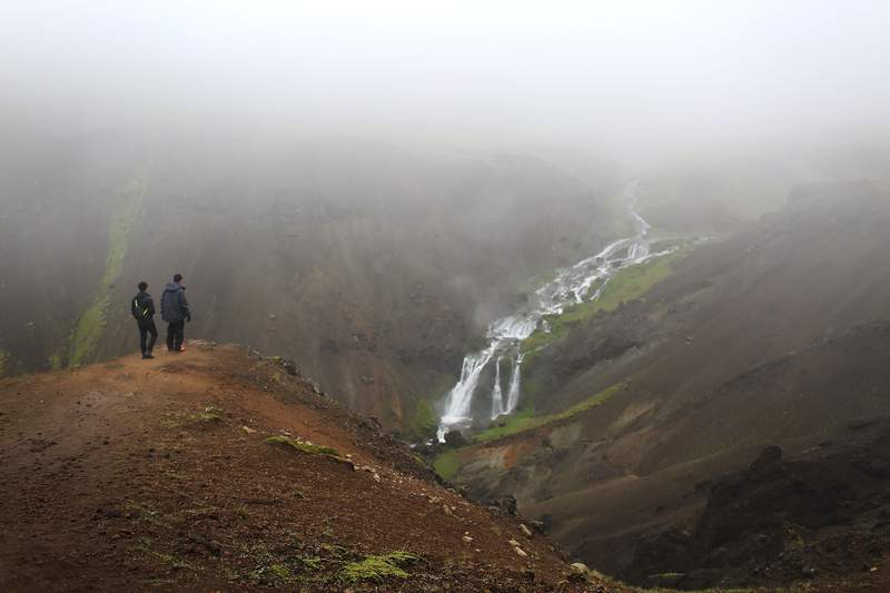 Visitors enjoy the views on a hike to the hot spring river in Hveragerdi, Iceland.