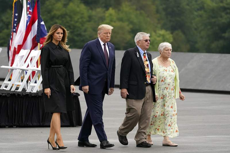 President Donald Trump and first lady Melania Trump walk with Ed Root and his wife Nancy to lay a wreath at a 19th anniversary observance of the Sept. 11 terror attacks, at the Flight 93 National Memorial in Shanksville, Pa., Friday, Sept. 11, 2020. Ed Root's cousin was flight attendant Lorraine Bay. (AP Photo/Alex Brandon)