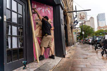 A worker boarded up windows on Sixth Street in Austin after Gov. Greg Abbott closed bars in Texas for the second time in three months because of the COVID-19 pandemic. (Credit: Jordan Vonderhaar for The Texas Tribune)