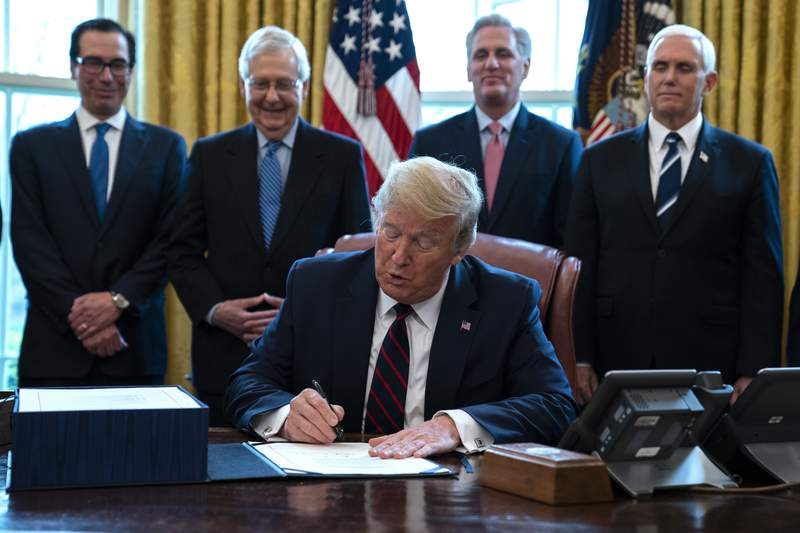 FILE - In this March 27, 2020 file photo, President Donald Trump signs the coronavirus stimulus relief package in the Oval Office at the White House in Washington, as Treasury Secretary Steven Mnuchin, Senate Majority Leader Mitch McConnell, R-Ky., House Minority Leader Kevin McCarty, R-Calif., and Vice President Mike Pence watch. Payments from a federal coronavirus relief package could take several weeks to arrive. While you wait, prep your finances and make a plan for using any money you receive.  (AP Photo/Evan Vucci, File)