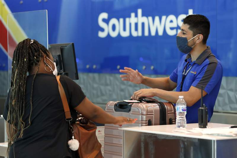 FILE - In this Wednesday, June 24, 2020, file photo, Southwest airlines employee Oscar Gonzalez, right, assists a passenger at the ticket counter at Love Field in Dallas. In a report, Thursday, July 2, 2020, the government is recommending that travelers wear face coverings during air travel and says airlines should consider limiting capacity on planes to promote social distancing. But it stopped short of making new requirements. (AP Photo/Tony Gutierrez, File)