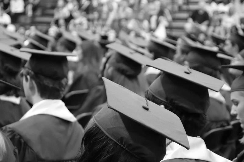 Students sit at a graduation.