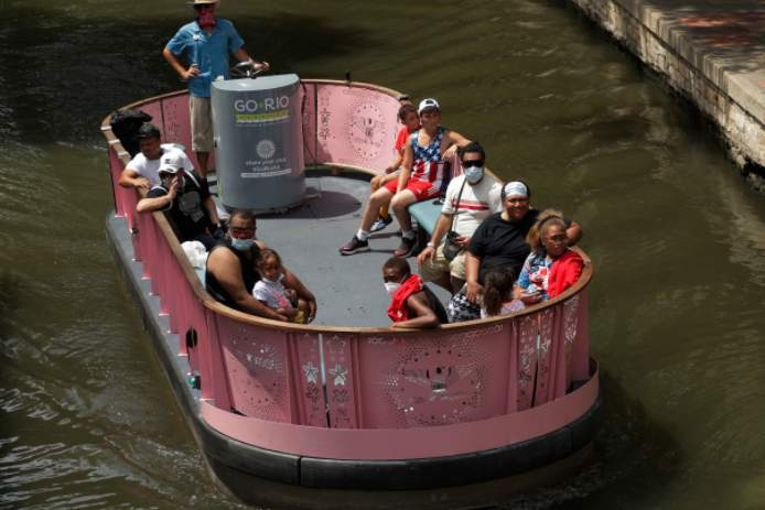 Visitors, some wearing masks to protect against the spread of COVID-19, ride a river barge along the River Walk, Tuesday, July 7, 2020, in San Antonio. (AP Photo/Eric Gay)