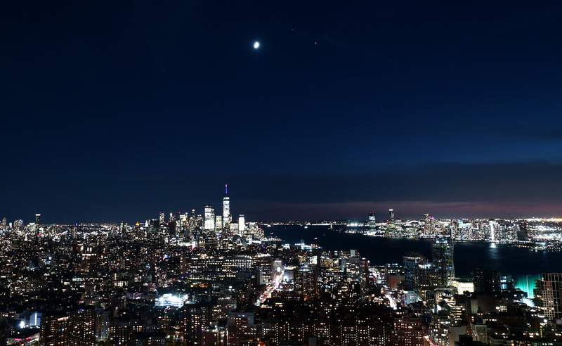 The moon, Saturn and Jupiter form a triangle as they rise over lower Manhattan and One World Trade Center as the sun sets on Nov. 19, 2020 in New York City.