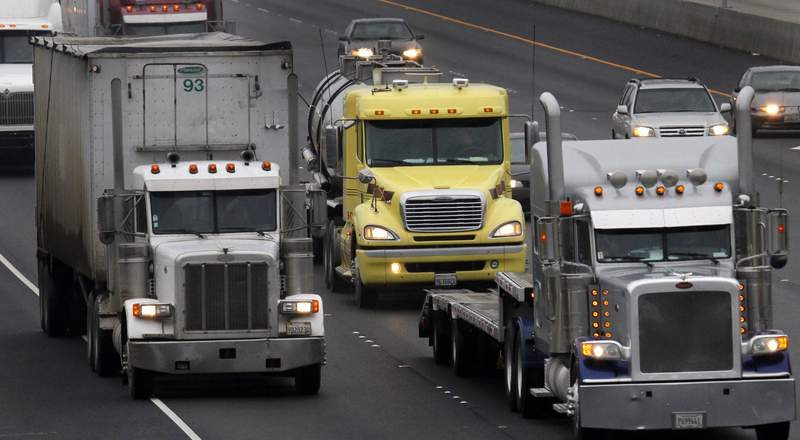 FILE 11 In this Dec. 17, 2010 file photo, trucks make their way eastbound, in Livermore, Calif. More than 75 national companies are throwing their weight behind a drive to make trucks, vans and other large commercial fleet vehicles cleaner as a climate change initiative. Several states, including Massachusetts, New Jersey, New York, Oregon and Washington, already are backing the move. (AP Photo/Ben Margot, File)