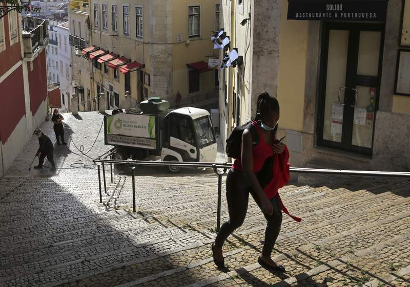 FILE - In this Wednesday, June 24, 2020 file photo, a woman wearing a face mask walks past workers washing the street in Lisbon's old center. A senior European human rights official is sounding the alarm about a rise in racism and discrimination in Portugal. The Council of Europes Commissioner for Human Rights, Dunja Mijatovi, published a report Wednesday, March 24, 2021 into the increasing level of racism and the persistence of related discrimination in the southern European country. (AP Photo/Armando Franca, File)
