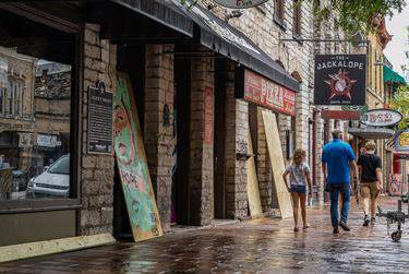 Workers boarded up bars on West 6th Street in Austin after Gov. Greg Abbott ordered them closed for the second time in three months on June 26. (Jordan Vonderhaar for The Texas Tribune)