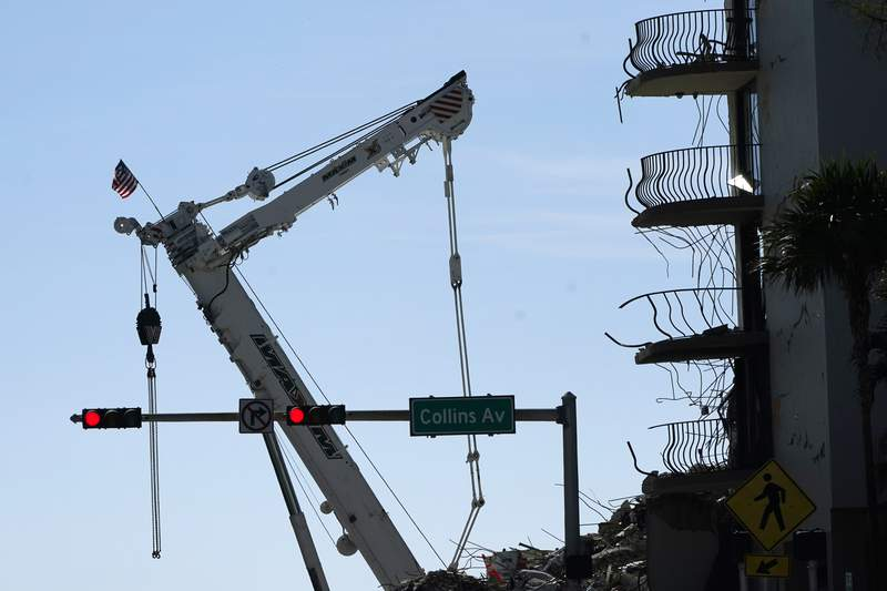 An American flag flies from a crane next to the Champlain Towers South condo building, where scores of victims remain missing more than a week after it partially collapsed, Sunday, July 4, 2021, in Surfside, Fla. Demolition teams are preparing to bring down the unstable remainder of the structure ahead of a tropical storm. (AP Photo/Lynne Sladky)