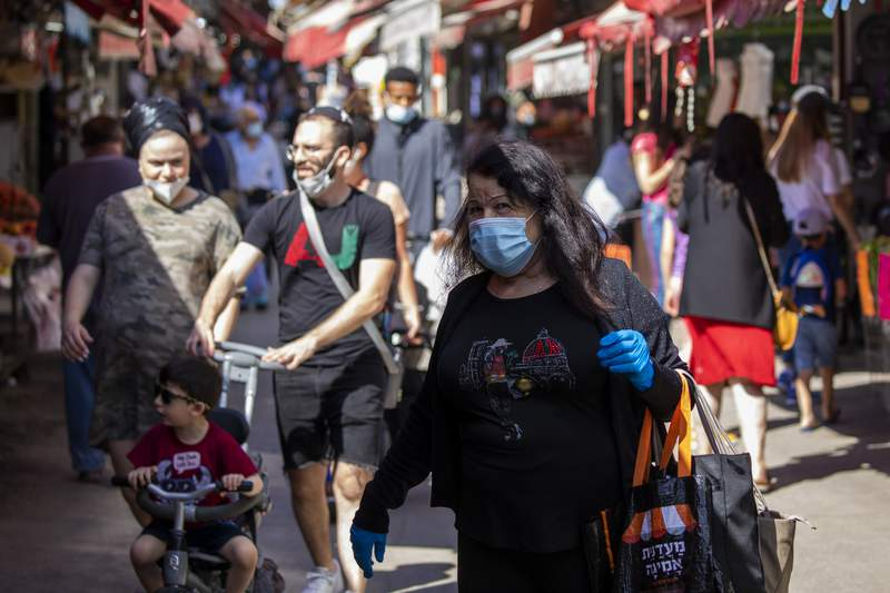 People wearing masks visit a food market that was shut down in order to reduce the spread of the coronavirus, as markets, shopping malls, gyms are reopen as Israel seeks to exit the virus lockdown in Tel Aviv, Israel, Thursday, May 7, 2020. (AP Photo/Ariel Schalit)