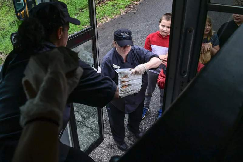 Culinary Services worker Ireida Montanez, left, hands Sharon Hughes meals for New Prospect Elementary School students along their bus route in Anderson, South Carolina. (USA TODAY NETWORK via Reuters Co.)