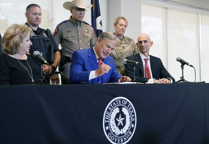 Texas Gov Greg Abbott, front center, is flanked by State Sen. Jane Nelson, R-Flower Mound, front left, and Rep. Greg Bonnen, R-Friendswood, front right, with others looking on as he signs a bill that provides additional funding for security at the U.S.-Mexico border Friday, Sept. 17, 2021, in Fort Worth. (AP Photo/LM Otero)