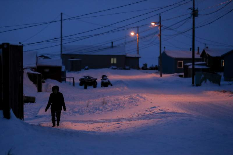 FILE - In this Jan. 20, 2020, file photo, a woman walks before dawn in Toksook Bay, Alaska, a mostly Yup'ik village on the edge of the Bering Sea. A judge has ruled in favor of tribal nations in their bid to keep Alaska Native corporations from getting a share of $8 billion in coronavirus relief funding  at least for now. In a decision issued late Monday, April 27, 2020, U.S. District Judge Amit Mehta in Washington, D.C., said the U.S. Treasury Department could begin disbursing funding to 574 federally recognized tribes to respond to the coronavirus but not to the corporations .(AP Photo/Gregory Bull, File)