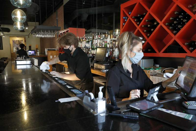 Deep Sushi restaurant employees Jordan Arrowood, left, cleans the bar top as Carrie Souza enters an order at the sushi restaurant in the Deep Ellum entertainment district in Dallas, Friday, June 26, 2020. Texas Gov. Greg Abbott announced Friday that he is shutting bars back down and scaling back restaurant capacity to 50%, in response to the increasing number of COVID-19 cases in the state. (AP Photo/Tony Gutierrez)