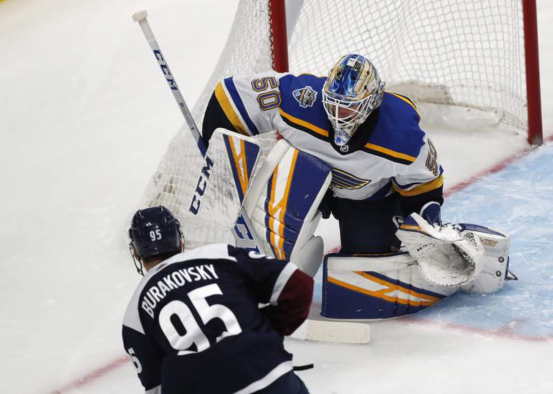 "FILE - In this Jan. 18, 2020, file photo, St. Louis Blues goaltender Jordan Binnington, back, stops a shot by Colorado Avalanche left wing Andre Burakovsky during the first period of an NHL hockey game in Denver. Obviously, last year gave us a lot of experience from top to bottom in the dressing room,"" said Binnington, the goaltender who came up clutch for the Blues last season as a rookie. Hopefully we can use that going into this year. (AP Photo/David Zalubowski, File)"