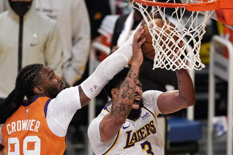 Los Angeles Lakers forward Anthony Davis, right, shoots as Phoenix Suns forward Jae Crowder defends during the first half in Game 4 of an NBA basketball first-round playoff series Sunday, May 30, 2021, in Los Angeles. (AP Photo/Mark J. Terrill)