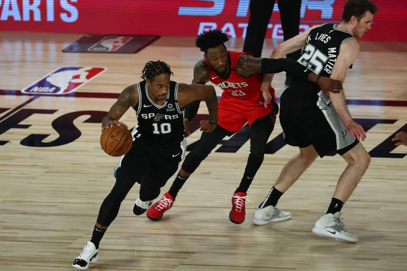 LAKE BUENA VISTA, FLORIDA - AUGUST 11: DeMar DeRozan #10 of the San Antonio Spurs drives past Robert Covington #33 of the Houston Rockets off a screen by Jakob Poeltl #25 of the San Antonio Spurs during the second half of a NBA basketball game at The Field House at ESPN Wide World Of Sports Complex on August 11, 2020 in Lake Buena Vista, Florida. NOTE TO USER: User expressly acknowledges and agrees that, by downloading and or using this photograph, User is consenting to the terms and conditions of the Getty Images License Agreement.  (Photo by Kim Klement-Pool/Getty Images)