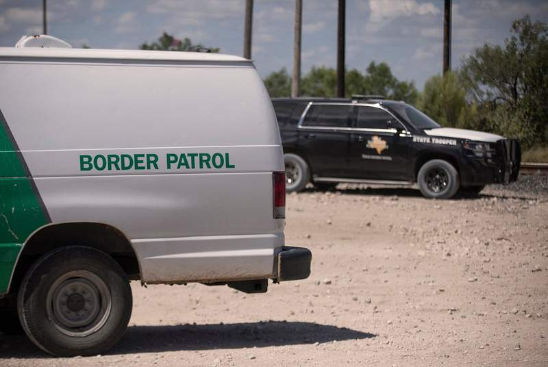 A Border Patrol van and a Texas Department of Public Safety vehicle parked near a train depot in Spoffard on Aug. 25, 2021.