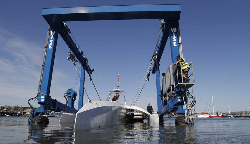 FILE - In this Monday, Sept. 14, 2020 file photo, technicians lower the Mayflower Autonomous Ship into the water at its launch site for it's first outing on water since being built in Turnchapel, Plymouth south west England. Four centuries and one year after the Mayflower departed from Plymouth, England on a historic sea journey to America, another trailblazing vessel with the same name has set off to retrace the voyage. Its being piloted by sophisticated artificial intelligence technology for a trans-Atlantic crossing that could take up to three weeks, in a project aimed at revolutionizing marine research. IBM, which built the ship with nonprofit marine research organization ProMare, confirmed the Mayflower Autonomous Ship began its trip early Tuesday June 15, 2021.(AP Photo/Alastair Grant, file)