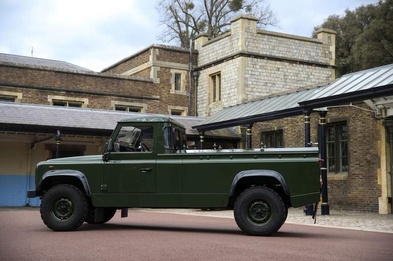 """The Jaguar Land Rover that will be used to transport the coffin of the Duke of Edinburgh at his funeral on Saturday, is pictured at Windsor Castle, in Berkshire, England, Wednesday, April 14, 2021. The modified Land Rover Defender TD5 130 chassis cab vehicle was made at Land Rover's factory in Solihull in 2003 and Philip oversaw the modifications throughout the intervening years, requesting a repaint in military green and designing the open top rear and special """"stops"""" to secure his coffin in place. (Steve Parsons/Pool Photo via AP)"""