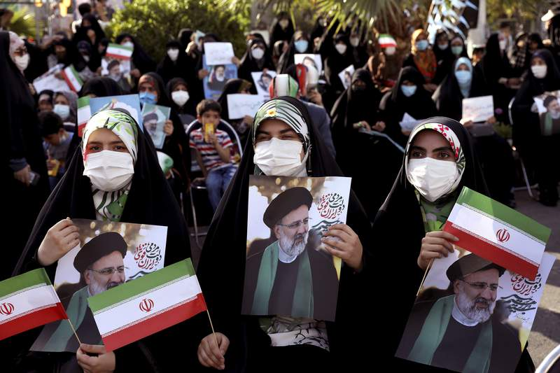 Supporters of presidential candidate Ebrahim Raisi hold signs during a rally in Tehran, Iran, Wednesday, June 16, 2021. Iran's clerical vetting committee has allowed just seven candidates for the Friday, June 18, ballot, nixing prominent reformists and key allies of President Hassan Rouhani. The presumed front-runner has become Ebrahim Raisi, the country's hard-line judiciary chief who is closely aligned with Supreme Leader Ayatollah Ali Khamenei. (AP Photo/Ebrahim Noroozi)