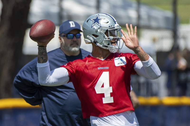 FILE - Dallas Cowboys quarterback Dak Prescott throws a pass as coach Mike McCarthy watches during the NFL football team's training camp in Oxnard, Calif., in this Thursday, July 22, 2021, file photo. From players getting COVID-19 vaccinations to relaxed coronavirus protocols to lineup issues, particularly at quarterback, the NFL faces a multitude of questions as training camps open. (AP Photo/Michael Owen Baker, File)