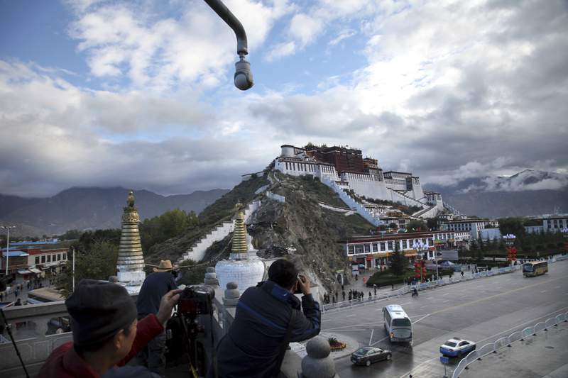 FILE - In this Sept. 19, 2015, file photo, tourists take photos of the Potala Palace beneath a security camera in Lhasa, capital of the Tibet Autonomous Region of China. China said Tuesday, May 19, 2020, that a boy who disappeared 25 years ago after being picked by the Dalai Lama as Tibetan Buddhism's second-highest figure is now a college graduate with a stable job. (AP Photo/Aritz Parra, File)